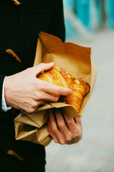 Freshly baked croissants from the bakery. male hand holding croissants in te paper bag.