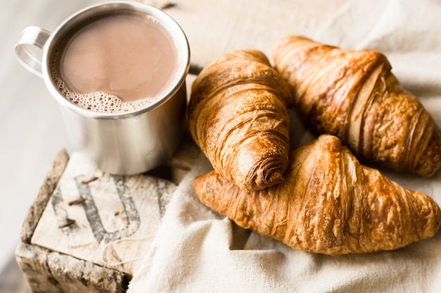 Freshly baked croissants on linen cloth, mug with hot cocoa on vintage wood box