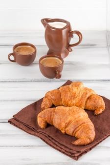 茶色のナプキン、クリーム、焼きたてのクロワッサン、白い木製の背景にセラミック皿にコーヒーのカップ。朝食に焼きたてのペストリー。美味しいデザート。クローズアップ写真。垂直バナー。