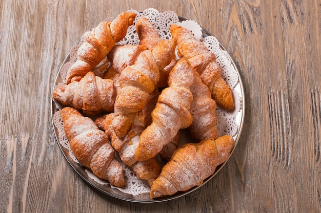 Freshly baked croissants on a round platter, top view. croissants on a wooden table