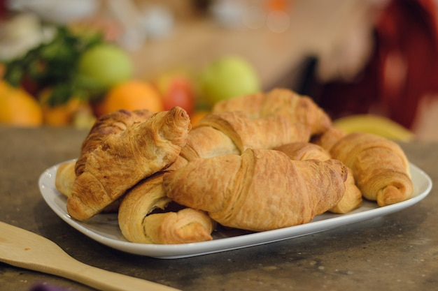 Freshly baked croissants on a white plate on a wooden table. delicious breakfast