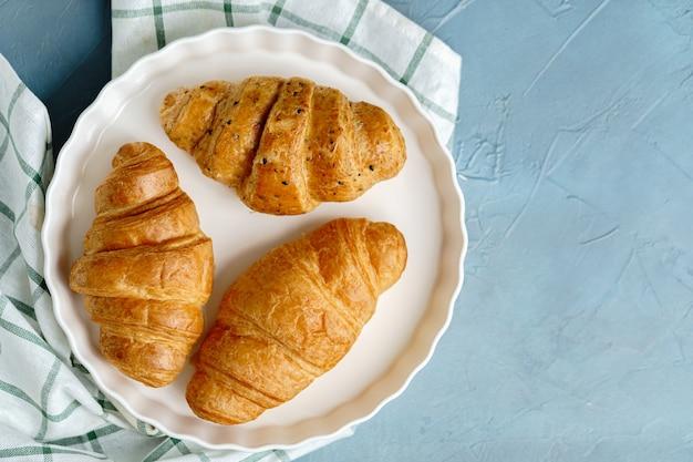Freshly baked croissants on white plate.