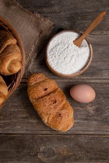 Croissant appena sfornati con uovo di gallina marrone e farina posti su un tavolo di legno. foto di alta qualità