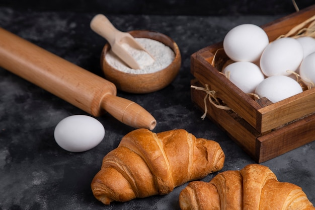 Freshly baked croissants with chicken eggs and kitchen utensils .