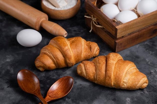 Croissant appena sfornati con uova di gallina e utensili da cucina.