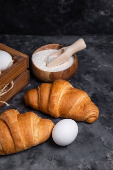 Freshly baked croissants with chicken eggs and wooden bowl of flour .