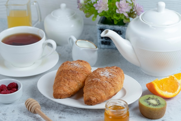 Freshly baked croissants with a cup of tea and sweet fruits .