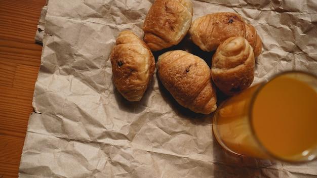 クラフト紙にオレンジジュースを添えた焼きたてのクロワッサン。朝食の新鮮なおいしいデザートのクローズアップ写真。