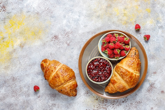Freshly baked croissants with raspberry jam and raspberry fruits.