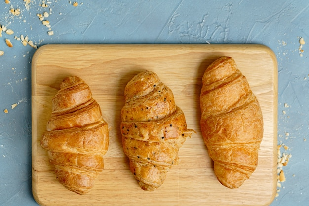 Freshly baked croissants on wooden plate, top view.
