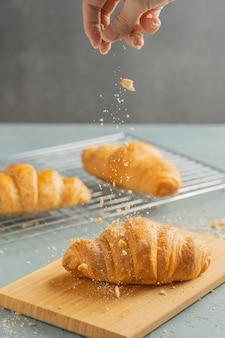 Freshly baked croissants on wooden plate.