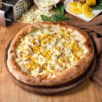 Свежеиспеченная корка гавайской пиццы с ветчиной и ананасом на деревянной доске в окружении ингредиентов по отдельности.