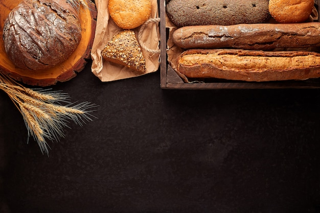Freshly baked delicious bread on a rustic wooden worktop with copy space