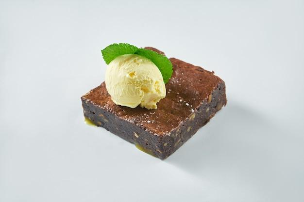焼きたてのデザート-白いプレートにバニラアイスクリームを添えたチョコレートブラウニー
