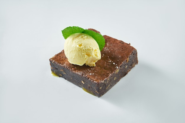 Freshly baked dessert - chocolate brownie with vanilla ice cream on a white plate