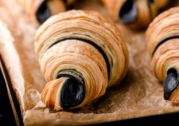 Freshly baked flaky croissants with chocolate on black metal tray on parchment