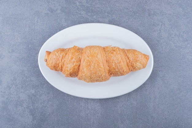 Freshly baked french croissant on white plate over grey background.