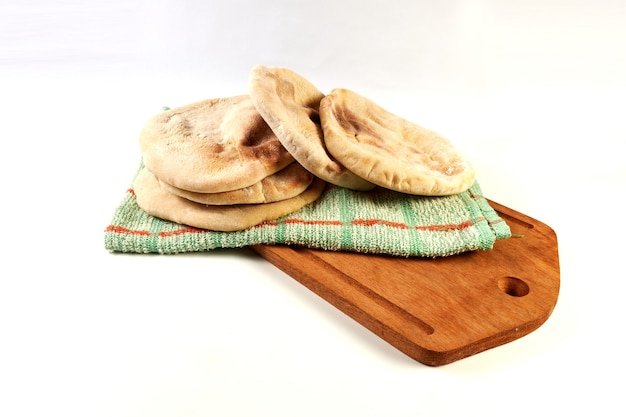Freshly baked, fresh pita, arabic breads on a rustic cloth and a wooden board on a white surface