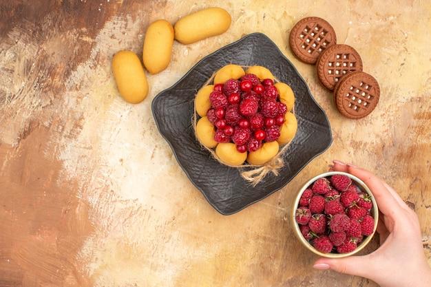 茶色のプレートビスケットの焼きたてのギフトケーキと混合色のテーブルのフルーツプレート
