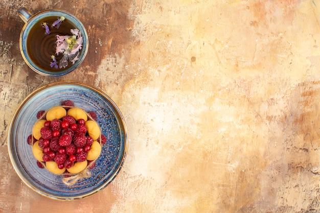 Torta regalo appena sfornata con frutta su un vassoio blu e una tazza di tè sulla tavola di colori misti