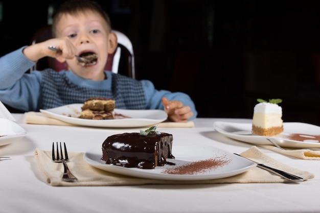 焼きたての艶をかけられたチョコレートケーキと濃厚なダークアイシングがデザートのプレートに添えられ、小さな男の子がバックグラウンドでケーキを食べています