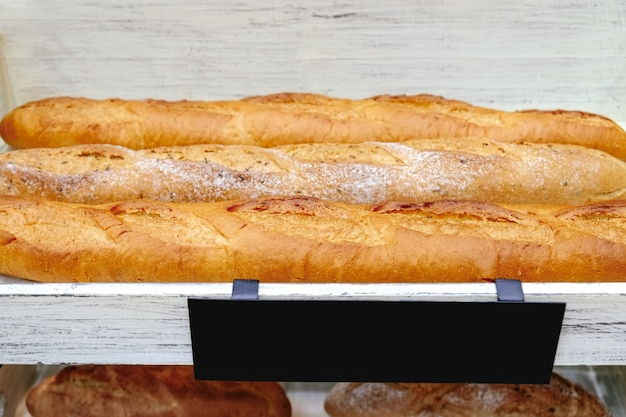 Freshly baked gluten free baguette breads on white wooden shelves with a blank black label tag.