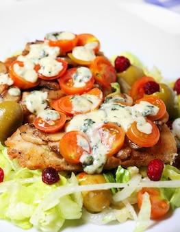Свежеиспеченная рыба хек с грибами, помидорами и голубым сыром на салате