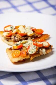 Свежеиспеченная рыба хек с грибами, помидорами и голубым сыром