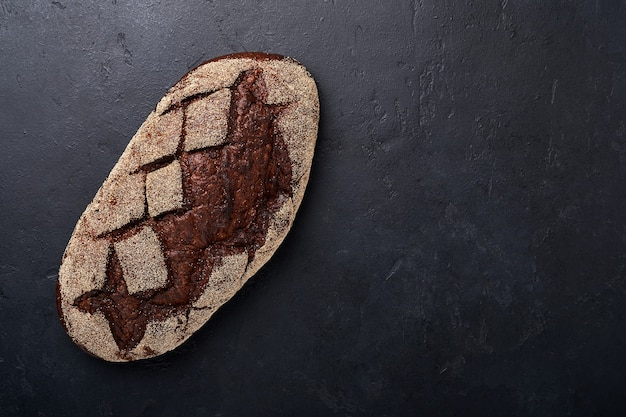 Freshly baked homemade bread on artisan sourdough rye on black stone or concrete background. top view. food cooking background. copy space.