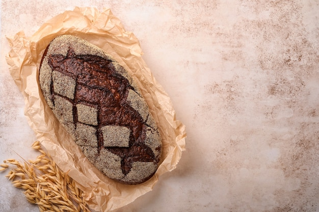 Freshly baked homemade bread on artisan sourdough rye on old light brawn stone or concrete background. top view. food cooking background. copy space.