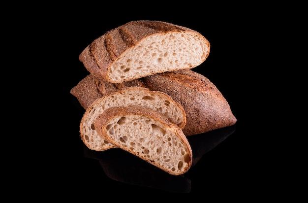 黒で隔離された焼きたての自家製パン。スライスしたライ麦パンを半分に切る。健康的な食事と伝統的なパン屋、パンのコンセプトを焼く。