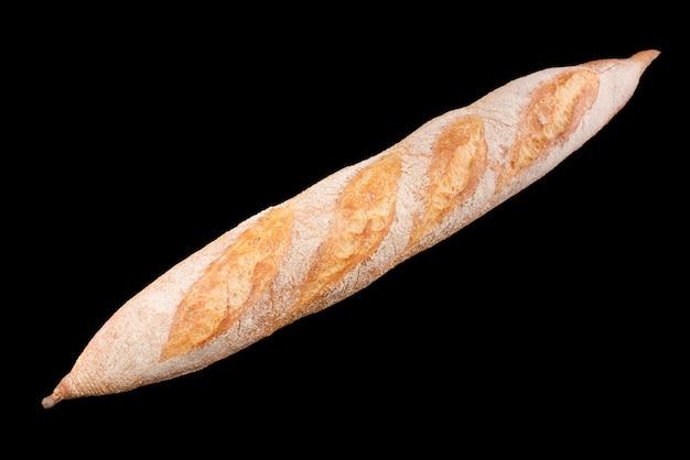 黒で隔離された焼きたての自家製パン。フランスパンバゲット。健康的な食事と伝統的なパン屋、パンのコンセプトを焼く。