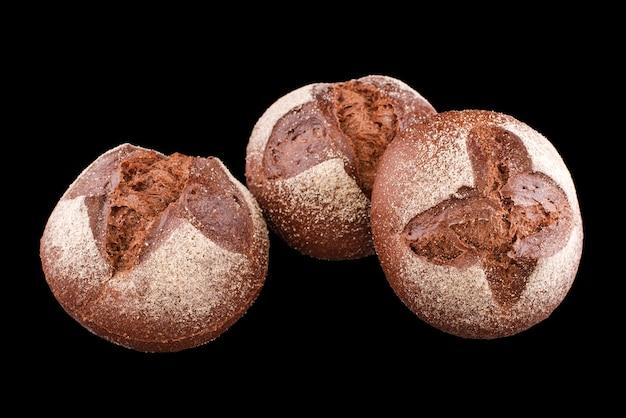 黒で隔離された焼きたての自家製パン。焼きたてのダークルーパン。健康的な食事と伝統的なパン屋、パンのコンセプトを焼く。