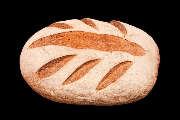 黒で隔離された焼きたての自家製パン。焼きたてのライ麦パン。健康的な食事と伝統的なパン屋、パンのコンセプトを焼く。