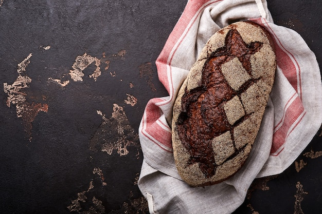 Свежеиспеченный домашний хлеб на ржаной закваске ручной работы на коричневом камне или бетонном фоне. вид сверху. еда приготовления фона. скопируйте пространство.