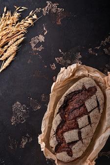 뻣뻣한 돌이나 콘크리트 배경에 장인의 사워도우 호밀에 갓 구운 홈메이드 빵. 평면도. 음식 요리 배경입니다. 공간을 복사합니다.