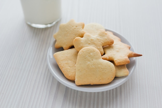 Freshly baked homemade cookies and a glass of milk on white wood