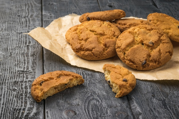 Freshly baked homemade cookies with chocolate chips on a piece of paper on a wooden table