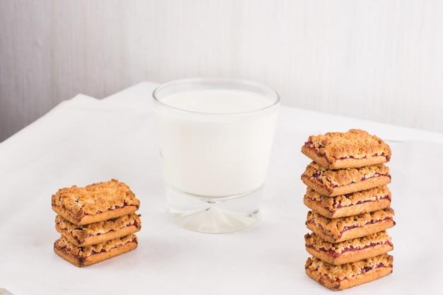 ガラスの牛乳とスタックのジャムと焼きたての自家製クッキー。バランスの取れた栄養、タンパク質と炭水化物、シリアル