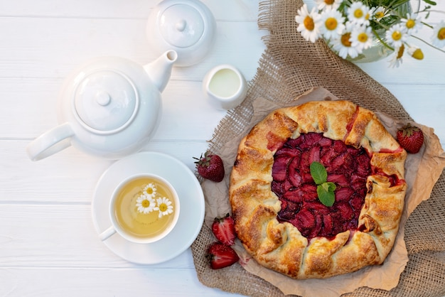 Freshly baked homemade galette or open strawberry pie, a cup of herbal tea, a teapot and a vase with a bouquet of daisy flowers.