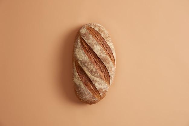 Pagnotta lunga fatta in casa appena sfornata isolata su sfondo beige. diversi ingredienti come farina, sale e lievito necessari per preparare il pane di grano bianco. concetto di cottura. prodotto necessario per mangiare