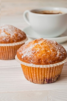 Freshly baked homemade muffins with sugar powder and a cup of coffee