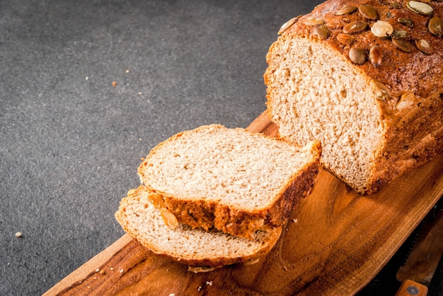Freshly baked homemade organic multi-grain bread with pumpkin seeds on a cutting board on a black stone table. copyspace