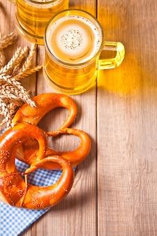 Свежеиспеченный домашний соль баварский крендель с rwo стакан пива на деревянный стол. вид сверху. копировать пространство