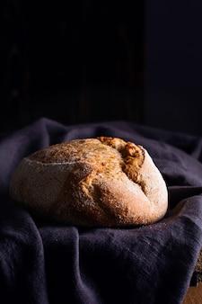 Freshly baked homemade sour dough bread on dark linen napkin, wooden.