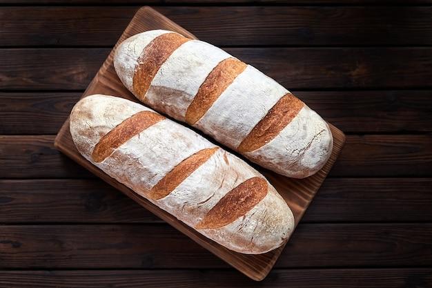 Свежеиспеченные домашние хлебцы пшеницы на деревянных фоне