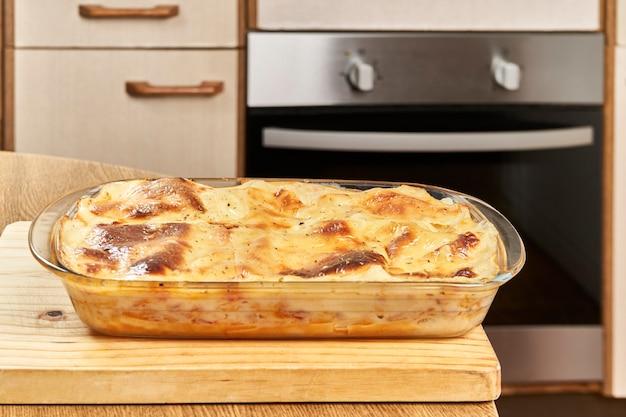 Свежеиспеченная горячая лазанья на деревянной доске на домашней кухне