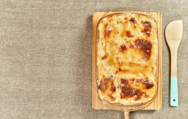 Свежеиспеченная горячая лазанья с плавленым сыром на деревенском столе