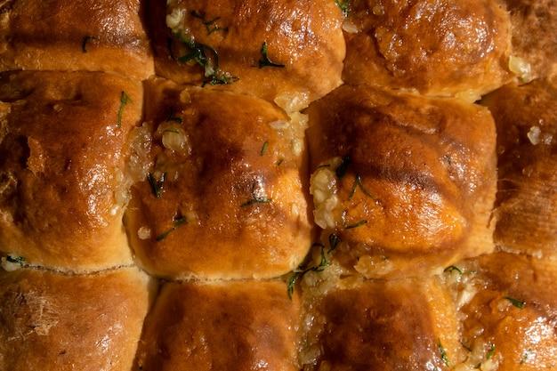 Свежеиспеченные горячие пшеничные булочки с чесноком остывают после духовки.