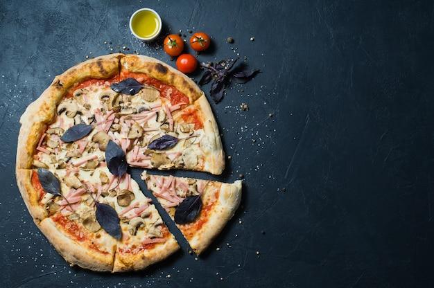 Freshly baked italian pizza with ham, mushrooms and basil.